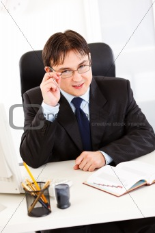 Smiling  businessman sitting at office desk and straightening eyeglasses