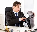 Shocked businessman sitting at office desk and searching something in briefcase