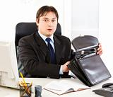 Shocked modern businessman sitting at office desk and holding open suitcase in hands