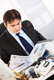 Serious businessman sitting at office desk and working  with financial documents