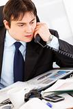 Concentrated businessman sitting at office desk and talking on phone