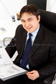Smiling businessman sitting at office desk and working  with financial documents