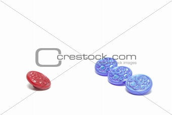 One red button and three blue ones isolated on white