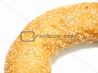 A part of bagel with sesame seeds on white