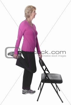 Active senior woman doing leg stretch with chair