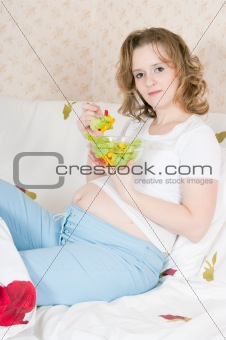 Pregnant woman in bed eating