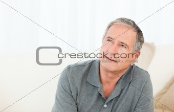 Mature man thoughtful with his walking stick on his bed