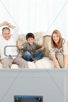 A little boy with his grandparents  in the living room