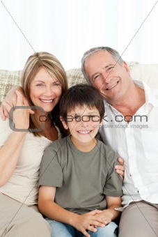 A little boy with his grandparents looking at the camera