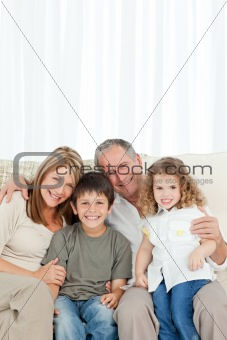 A happy family on their sofa looking at the camera
