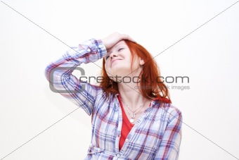 Redhead young woman holding her hand to the head