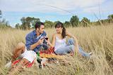 happy couple enjoying countryside picnic in long grass