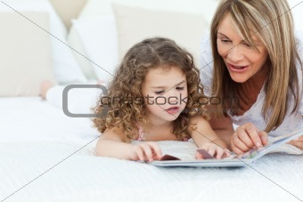 A grandmother and her granddaugher reading a book