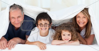 Family in their bedroom looking at the camera at home