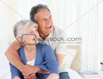 Senior couple hugging on their bed