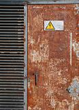 High voltage sign on a rusty door