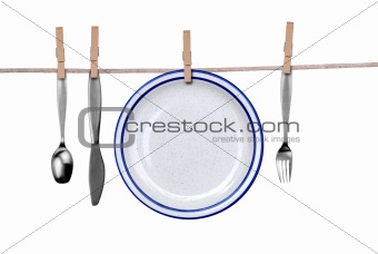 Fork, knife, spoon and plate on clothesline