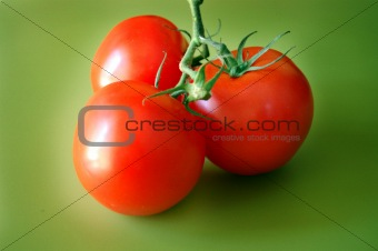 Tomatoes on green background