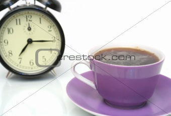 Cup from coffee and a black alarm clock