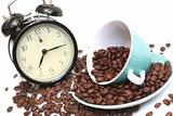 Cup with coffee grains and a black alarm clock
