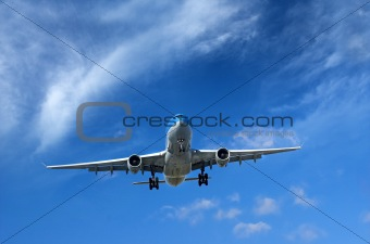 Airliner under wispy clouds