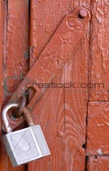 Old lock on red wooden door