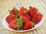 Appetizing large strawberry on a white plate