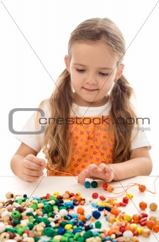Little girl playing with string and beads