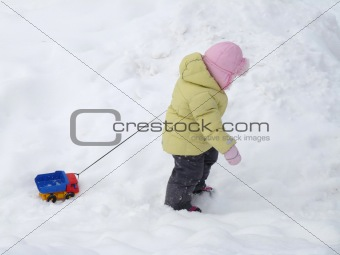 A child carries toy car in the snow