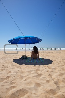 blue parasol with woman sit on towel