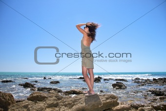 pretty woman walking on rocks next ocean