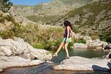 walking woman on a rock at a Gredos river