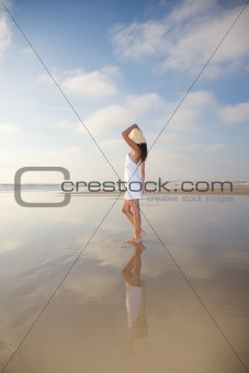woman reflected on wet sand
