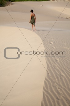 woman walking at sand curve