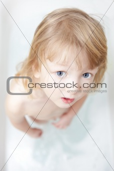 boy with long blong hair standing in bathtub looking up