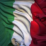 Flag of Italy, fluttering in the breeze, backlit rising sun