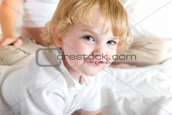 Boy playing in mothers bed