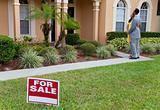 African American Couple Beside House For Sale Sign