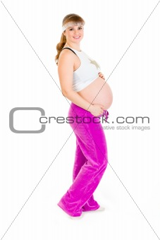 Smiling beautiful pregnant woman in sportswear holding her tummy