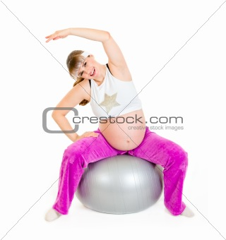 Smiling beautiful pregnant woman doing exercises on fitness ball