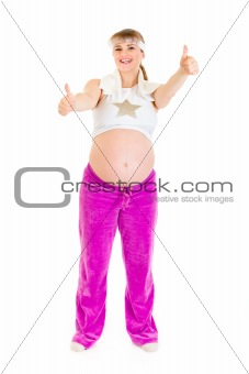 Smiling beautiful pregnant woman in sportswear showing thumbs up gesture