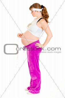 Beautiful pregnant woman measuring her belly