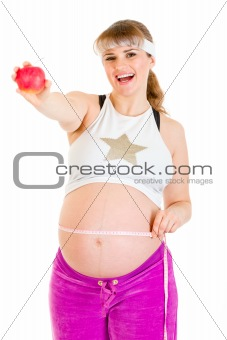 Smiling beautiful pregnant woman measuring her belly and holding apple