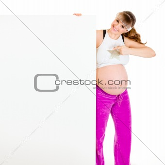 Smiling beautiful pregnant woman pointing finger at blank billboard