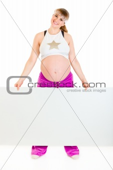 Smiling beautiful pregnant woman holding blank billboard