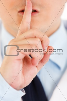 Medical doctor with finger at mouth. Shh gesture