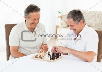 Senior men playing chess at home