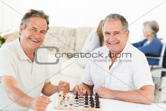 Men playing chess while their wifes are talking