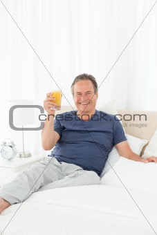 Retired man looking at the camera while he is drinking orange juice