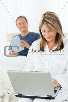 Woman looking at her laptop while her husband is reading
